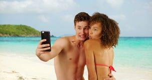 Mâle caucasien beau avec l'ami féminin prenant le selfie sur la plage Photo stock