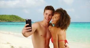 Mâle caucasien beau avec l'ami féminin prenant le selfie sur la plage Image libre de droits
