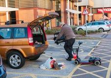 Mâle chargeant un scooter diabled de mobilité de personnes dans le dos de Images libres de droits