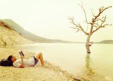 Mâle détendant par un lac lisant les pieds nus d'un livre Images libres de droits