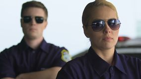 Mâle déterminé et policiers féminins dans des lunettes regardant à la caméra, équipe banque de vidéos