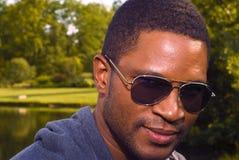 Mâle d'Afro-américain en nature avec des lunettes de soleil Photo stock