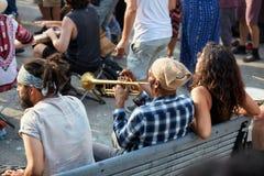 Mâle d'afro-américain s'asseyant sur un banc et une trompette de soufflement au festival de Tam Tams en parc royal de bâti photo stock