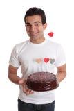 Mâle d'amusement de Valentine avec le gâteau de coeur de chocolat Photo stock