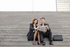 mâle d'ingénieurs et article femelle de lecture concernant la société dedans Image stock