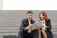 mâle d'ingénieurs et article femelle de lecture concernant la société dedans Photos stock