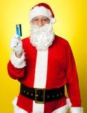 Mâle dans le costume de Santa posant avec sa carte d'argent comptant Photographie stock libre de droits
