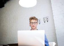 Mâle dans le développement réussi en verre des projets numériques utilisant le filet-livre portatif Photographie stock libre de droits
