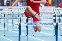 Mâle de lycée participant à une course d'obstacles de 110 mètres Image libre de droits