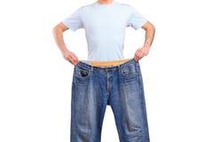 Mâle de perte de poids affichant ses vieux jeans image libre de droits