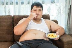 Mâle de poids excessif paresseux s'asseyant avec les aliments de préparation rapide Photo stock