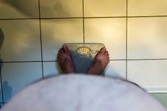 Mâle de poids excessif sur des échelles Photographie stock libre de droits