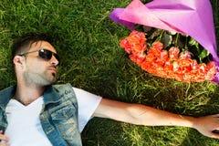 Mâle de sourire de valentine avec le groupe de roses se trouvant sur l'herbe photographie stock libre de droits