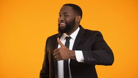 Mâle drôle d'afro-américain dans le costume faisant des pouces- et clignant de l'oeil la qualité de service clips vidéos