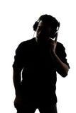 Mâle en silhouette écoutant des écouteurs Photo libre de droits