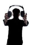 Mâle en silhouette montrant des écouteurs Images stock