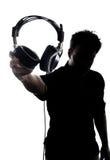 Mâle en silhouette montrant des écouteurs Photos stock