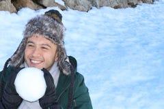Mâle espiègle environ pour jeter une boule de neige Photographie stock libre de droits