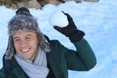 Mâle espiègle environ pour jeter une boule de neige Images stock