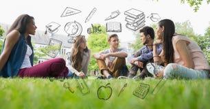 Mâle et étudiantes s'asseyant sur l'herbe avec les graphiques éducatifs Images libres de droits