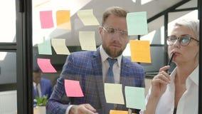 Mâle et collègues exécutifs féminins faisant un brainstorm le projet dans le lieu de réunion de bureau clips vidéos