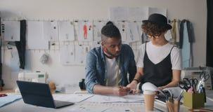 Mâle et concepteurs féminins communiquant vérifiant des croquis utilisant l'ordinateur portable banque de vidéos