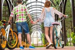 Mâle et femelle avec des vélos tenant des mains dans l'arcade Photos stock