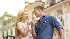 Mâle et femelle dans l'amour mangeant la crème glacée et regardant l'un l'autre, espiègle Photos libres de droits