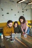 Mâle et femelles de hippie de Yong en café fonctionnant avec l'ordinateur portable Images stock