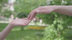 Mâle et mains femelles se touchant dans le plan rapproché de premier plan Beau parc vert sur le fond loisirs banque de vidéos