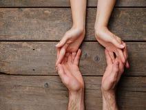 Mâle et mains femelles sur le fond en bois avec l'espace de copie photographie stock libre de droits