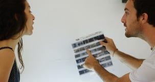 Mâle et photographes féminins vérifiant des bandes de film avec la loupe 4k banque de vidéos