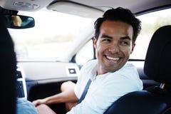 Mâle gai heureux parlant avec des passagers tout en se reposant dans l'automobile confortable Image stock