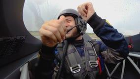 Mâle heureux dans l'habitacle des mains d'avion à réaction et de représentation des pouces de ondulation mobiles  banque de vidéos
