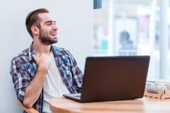 Mâle heureux, s'asseyant dans un café avec un ordinateur portable, riant et regardant la fenêtre Images libres de droits