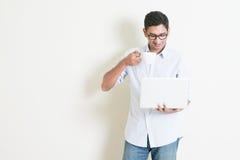 Mâle indien d'affaires occasionnelles utilisant l'ordinateur portable et le café potable Photo libre de droits