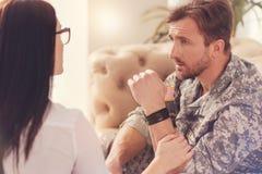Mâle militaire sérieux parlant avec son psychologue photos stock