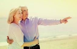 Mâle montrant à son épouse quelque chose dans la distance au bord de la mer Image libre de droits