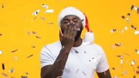 Mâle noir dans le chapeau de Santa envoyant le baiser d'air à la caméra sous les confettis en baisse, partie banque de vidéos