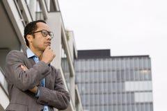 Mâle occasionnel intelligent pensant en dehors de l'immeuble de bureaux Photos stock