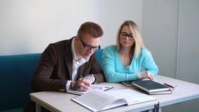 Mâle positif et étudiantes faisant le travail passant ensemble le temps dans le campus, collègues notant créatif banque de vidéos