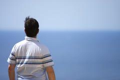Mâle regardant à l'extérieur à la mer Photos stock