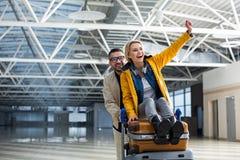 Mâle riant et divertissement femelle avec le chariot de bagages Photographie stock libre de droits