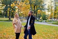 Mâle roux et femelle blond ayant l'amusement dans le parc de ville d'automne Photos libres de droits