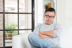 Mâle 50s asiatique mûr s'asseyant à la maison Images stock
