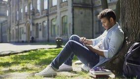 Mâle s'asseyant sous l'arbre, utilisant le téléphone portable, réagissant à la distribution d'articles Usenet, confusion banque de vidéos