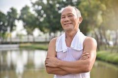 Mâle supérieur asiatique posant avec des bras croisés Photo stock
