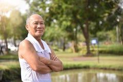 Mâle supérieur asiatique posant avec des bras croisés Photos stock