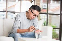Mâle supérieur asiatique prenant des pilules Photographie stock