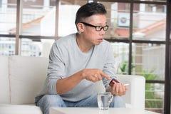 Mâle supérieur asiatique prenant des pilules Photos stock